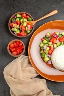 Verticale weergave van veganistisch diner met rijst en verschillende soorten groenten op zwart