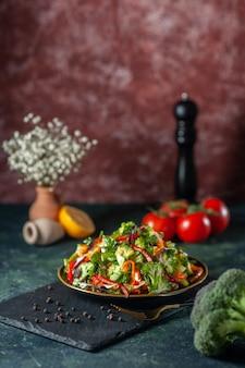 Verticale weergave van veganistische salade met verse ingrediënten in een bord en peper op zwarte snijplank