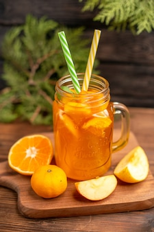 Verticale weergave van vers vruchtensap in een glas geserveerd met buizen en appel en sinaasappel op een houten snijplank op een bruine tafel