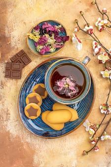Verticale weergave van verschillende koekjes een kopje thee en bloemen chocoladerepen op gemengde kleurentafel
