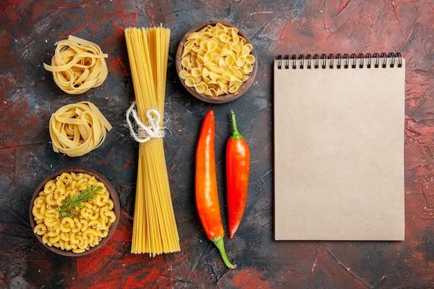 Verticale weergave van verschillende soorten ongekookte pasta's en paprika's op gemengde kleurenachtergrond