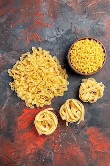Verticale weergave van verschillende soorten ongekookte pasta's op gemengde kleurenachtergrond
