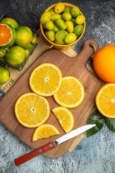 Verticale weergave van verse citrusvruchten met mes op houten snijplank op krant op grijze achtergrond