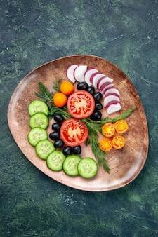 Verticale weergave van verse gehakte groenten olijven kumquats in een bruine plaat op groen zwart gemengde kleuren achtergrond