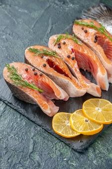 Verticale weergave van verse rauwe vissen greens peper en citroen plakjes op donkere kleur lade op blauw zwart mix kleuren tafel