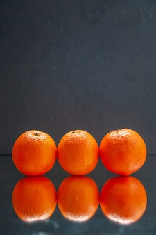 Verticale weergave van verse sinaasappelen die naast elkaar staan op een zwarte achtergrond met vrije ruimte