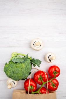 Verticale weergave van verse tomaten met stengel champignons broccoli in een mand op witte achtergrond