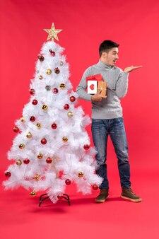 Verticale weergave van verwarde knappe man die in de buurt van de versierde witte kerstboom en zijn geschenken op rood houdt