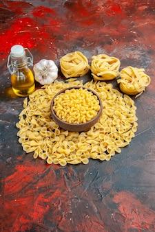 Verticale weergave van vlinder ongekookte pasta's in een bruine kom spaggeti knoflook en olie fles op gemengde kleur achtergrond