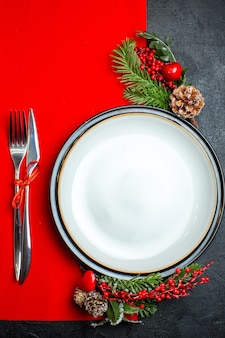 Verticale weergave van xsmas achtergrond met diner plaat decoratie accessoires fir takken en bestek ingesteld op een rood servet