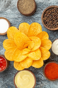 Verticale weergave van zelfgemaakte aardappelchips ingericht als bloem gevormd in een bruine kom op grijze achtergrond