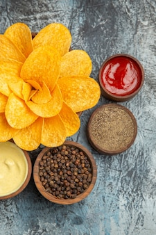 Verticale weergave van zelfgemaakte aardappelchips ingericht als bloem vormige verschillende kruiden en ketchup op grijze achtergrond