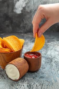 Verticale weergave van zelfgemaakte heerlijke knapperige chips in een bruine kom mayonaiseketchup op grijze achtergrond