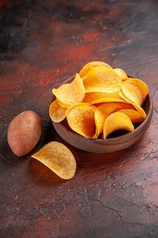 Verticale weergave van zelfgemaakte heerlijke knapperige chips in een kleine bruine kom aan de linkerkant van een donkere achtergrond