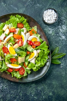 Verticale weergave van zelfgemaakte heerlijke salade met veel ingrediënten in een plaat en zout op zwarte groene mix kleuren achtergrond