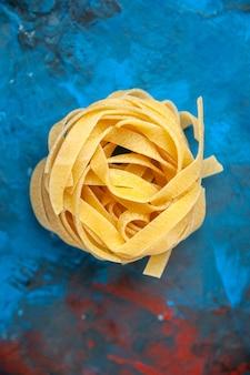 Verticale weergave van zelfgemaakte verse tagliatelle pasta op blauwe achtergrond