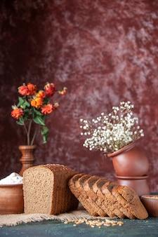 Verticale weergave van zwart brood, sneetjes meel in een kom en tarwe op naakte kleurhanddoek en bloempotten op gemengde kleurenachtergrond