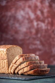 Verticale weergave van zwart brood sneetjes mes op donkere kleur bord op kastanjebruine noodlijdende achtergrond