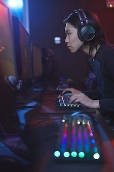 Verticale zijaanzicht portret van jonge aziatische man met behulp van computer in cyber hacking studio, kopieer ruimte