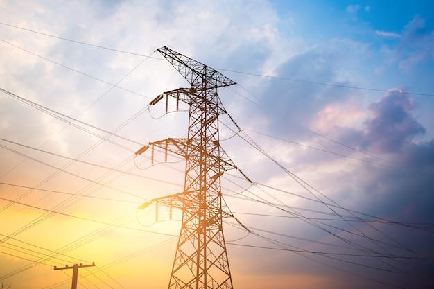 Vertoningsnetwerk bij transformatorstation in zonsopgang, hoogspanning tot gele hemel nemen met gele toon