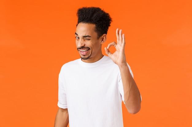 Vertrouw op mij. uitgaande ontspannen en zelfverzekerde jonge aantrekkelijke afro-amerikaanse mannen moedigen aan, assertief zijn, goed teken en knipoog tonen, geruststellen dat alles goed is, oranje