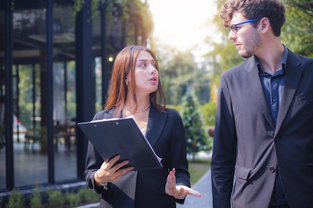 Vertrouwelijke jonge zakenmensen lopen en praten buiten het kantoor, plannen en discussiëren over een nieuw project met de partner