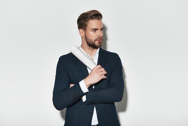 Vertrouwen en charisma. knappe jonge man in volledig pak die zijn armen gekruist houdt en wegkijkt terwijl hij tegen een grijze achtergrond staat