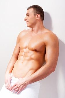 Vertrouwen in zijn lichaam. zijaanzicht van een zelfverzekerde jonge shirtloze man bedekt met een handdoek die wegkijkt en glimlacht terwijl hij tegen de muur leunt