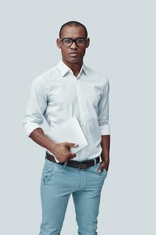Vertrouwen. knappe jonge afrikaanse man die digitale tablet gebruikt en naar de camera kijkt terwijl hij tegen een grijze achtergrond staat
