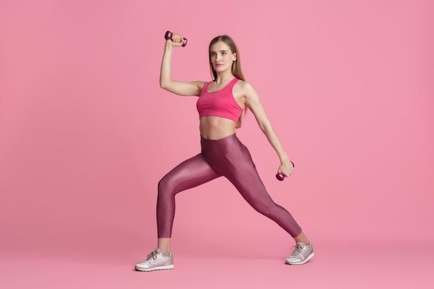 Vertrouwen. mooie jonge vrouwelijke atleet oefenen in studio, zwart-wit roze portret.