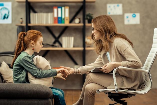 Vertrouwen ontwikkelen. aardige vriendelijke vrouw die een meisjeshand vasthoudt terwijl ze vertrouwen met haar ontwikkelt