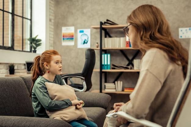 Vertrouwen opbouwen. aardig verdrietig meisje dat naar haar dokter kijkt terwijl ze klaar is om haar problemen te delen