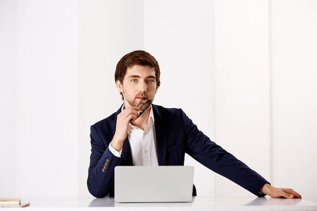 Vertrouwen, stijlvolle zakenman in pak, zit bureau in de buurt van laptop, nadenkend
