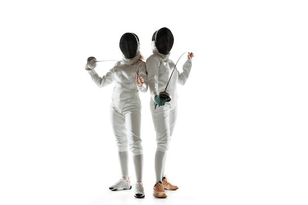 Vertrouwen. tienermeisjes in kostuums schermen met zwaarden in handen op witte achtergrond. jonge vrouwelijke modellen oefenen en trainen in beweging, actie. copyspace.
