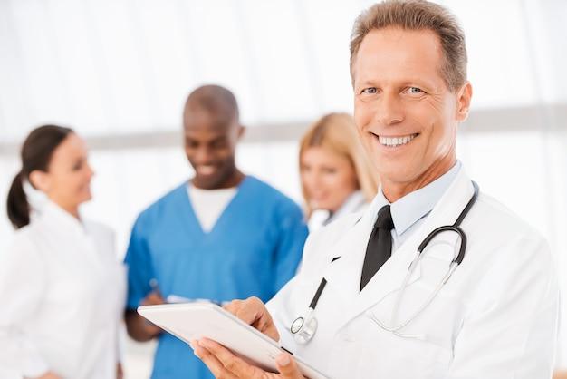 Vertrouwen voelen in zijn collega's. zelfverzekerde arts die aan digitale tablet werkt en glimlacht terwijl zijn collega's op de achtergrond praten