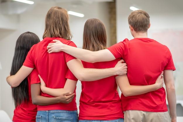 Vertrouwen. vriendelijke vrijwilligers in rode t-shirts knuffelen staan met hun rug naar camera in verlichte kamer