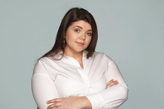 Vertrouwen, zaken, mensen en levensstijlconcept. zelfverzekerde jonge vrouw met overgewicht met mollige wangen en natuurlijke make-up poseren met gekruiste armen op haar borst, uiting van onwil