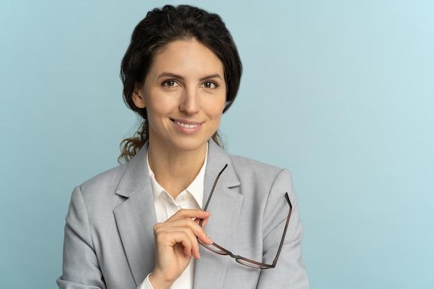 Vertrouwen zakenvrouw bedrijf bril, glimlachen, camera poseren geïsoleerd op blauwe achtergrond kijken.