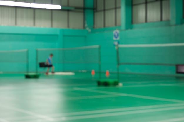Vervaag badmintonvelden zonder dat spelers strijden tegen moderne sportschool op de achtergrond, deselectieve focus. badminton gymp binnensport.