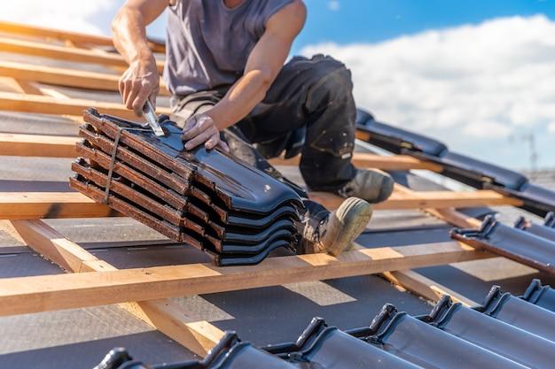 Vervaardiging van het dak van een gezinswoning uit keramische tegels. kopieer ruimte