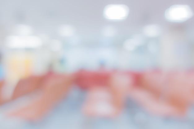 Vervagen afbeelding achtergrond van de receptie van ziekenhuis of kliniek met mensen en stoel
