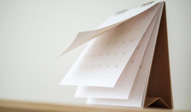 Vervagen agendapagina blad op houten tafel achtergrond zakelijke planning planning afspraak vergadering concept