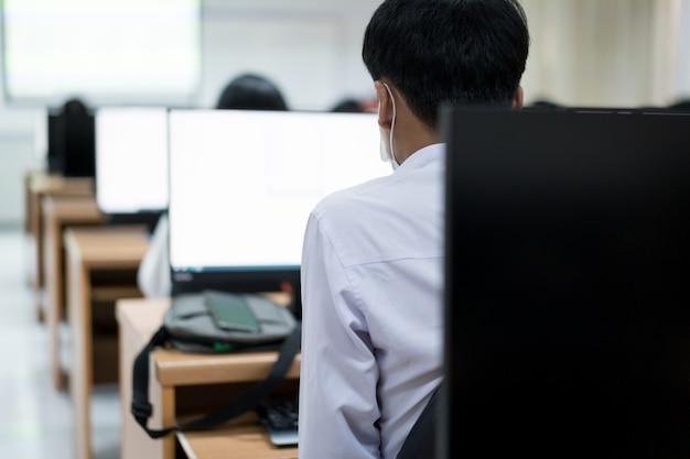 Vervagen en selectieve focus van de universiteitsstudent met behulp van computer studeren in de computerruimte. groep studenten studeren in de computerruimte. serieuze studenten die op computers aan de universiteit werken.