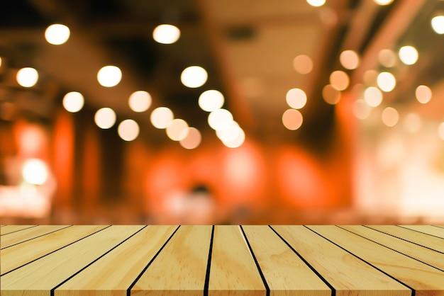 Vervagen interieur restaurant café met lampen lamp licht op plafond en houten tafel voor ontwerpconcept