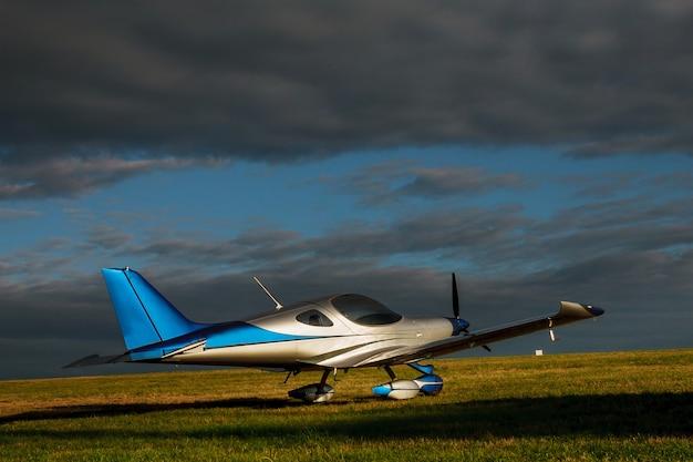 Vervagen licht klein vliegtuig op een grasveld op een achtergrond van blauwe wolken