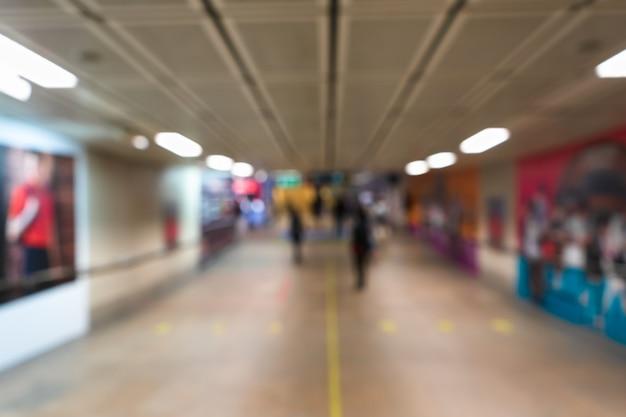 Vervagen loop manier platform in moderne metro. vervagen abstract achtergrondconcept. ondergrondse wandelpad in stedelijke stad met wazig reclamebord.