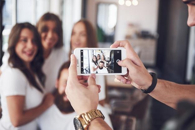 Vervagen portret van zalige jonge beste vrienden met handen met telefoon op voorgrond.