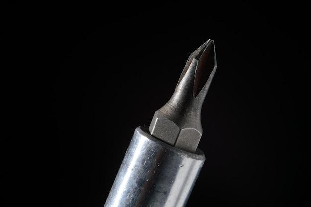 Vervangbare bit phillips schroevendraaier op een zwarte achtergrond close-up.