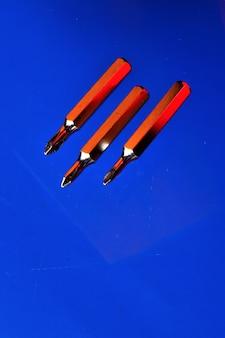 Vervangbare bits voor een kleine schroevendraaier liggen op een blauwe achtergrond.