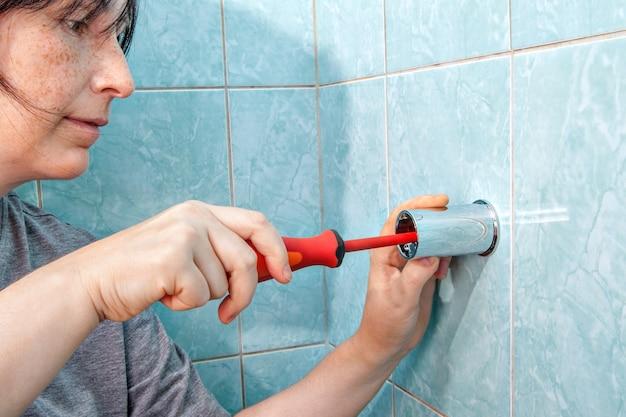 Vervangen sanitair in badkamer, vrouw bevestigd aan wandhouder voor douche, met schroevendraaier.